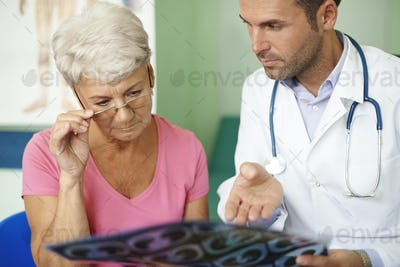 Doctor with his senior patient analyzing medical test