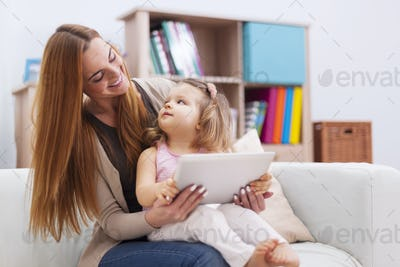 Mother and baby playing games on the tablet at home