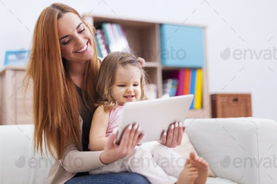 Mother with little daughter enjoying the free net at home