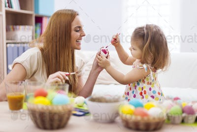 Happy mother helping baby painting on easter eggs