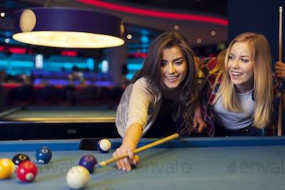 Two female friends enjoying pool game