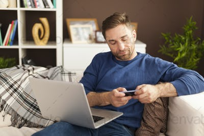Focus man using mobile phone and laptop at home