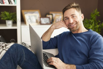 Portrait of smiling man with laptop on sofa