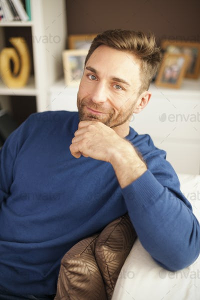 Portrait of handsome man sitting on sofa