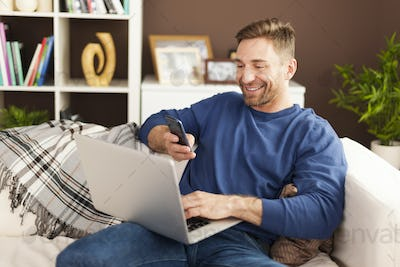 Happy man scanning qr code by mobile phone at home