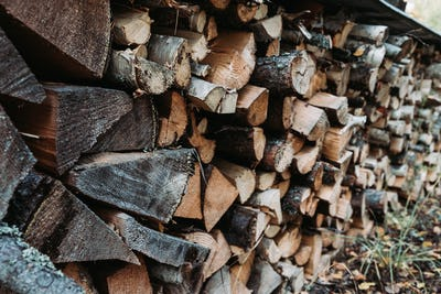 A large stack of firewood for the winter at outdoor. Rustic lifestyle background.