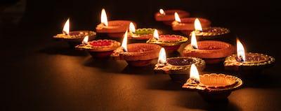 Diwali, Hindu festival of lights celebration. Diya oil lamps against dark background,