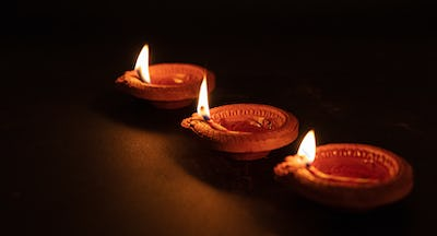 Happy Diwali. Diya colorful oil lamps, dark background