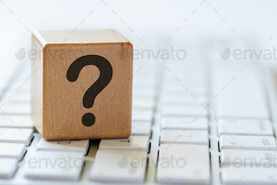 Small wooden dice with question mark on keyboard