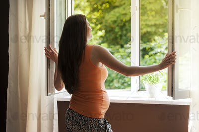 Pregnant woman opening window in living room