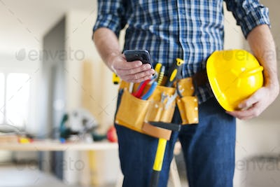 Close up of construction worker with mobile phone