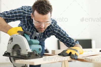 Hard working carpenter cutting wooden plank