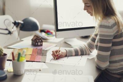 Creative interior designer sketching on a house plan