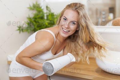 Portrait of beautiful blonde woman drying hair in bathroom