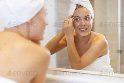 Woman tweezing eyebrows in front of mirror
