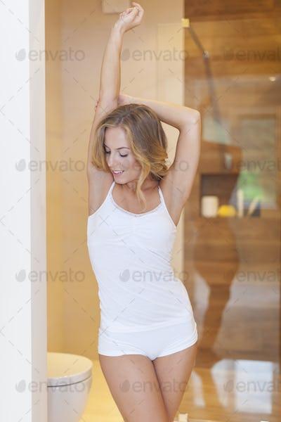 Woman wearing in pajamas stretching in bathroom