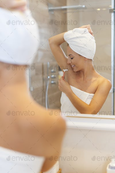 Woman shaving armpit after the shower