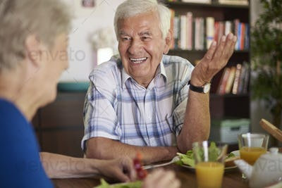 Cheerful senior marriage eating breakfast together