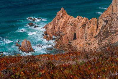Praia do Ursa beach with beautiful orange colored cliffs on Atlantic ocean coast near popular