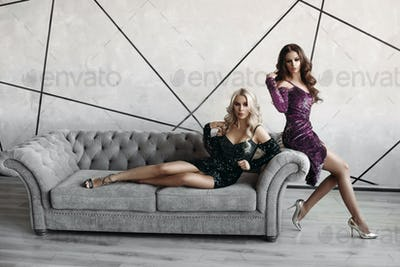 Two stunning women in evening dress posing on luxurious grey couch