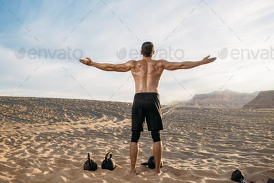 Sportsman with weights in desert, back view