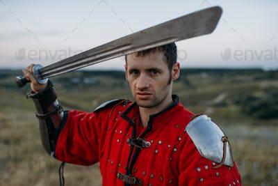 Medieval knight in metal helmet holds sword