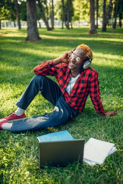 Black student in headphones sitting on the grass