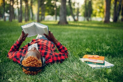 Black student resting on the grass, top view