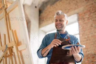 Happy and successful painter with palette looking at painting on easel