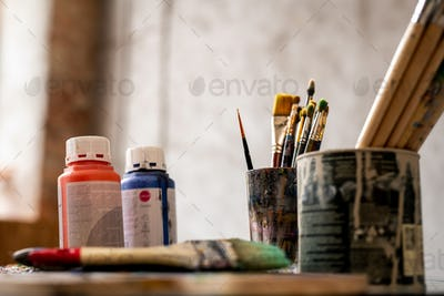 Set of paintbrushes in tin cans and two plastic jars with red and blue gouache