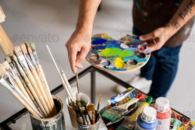 Painter holding palette with mixed colors and putting paintbrush in water