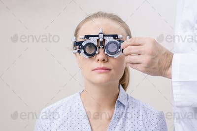 Young woman having her eye vision examined while looking through optometric lens