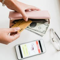 Hands of young woman holding leather wallet with dollar bills and plastic card