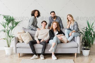 Joyful intercultural teenagers in casualwear relaxing on sofa together