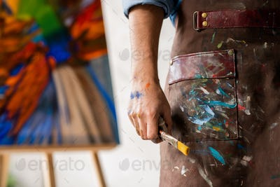 Part of professional painter in dirty apron holding paintbrush in hand