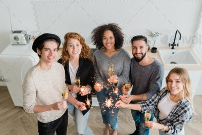 Young cheerful friends with flutes of champagne and sparkling bengal lights