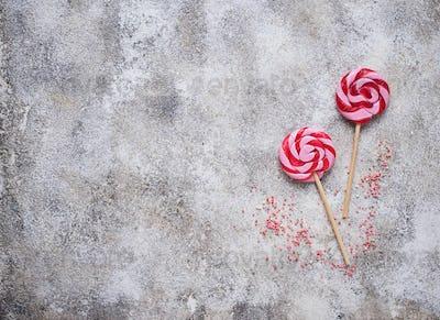 Pink lollipop on light background