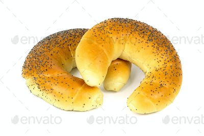 Crescent rolls with poppy seeds on white background