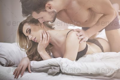 Erotic moments of couple in bed