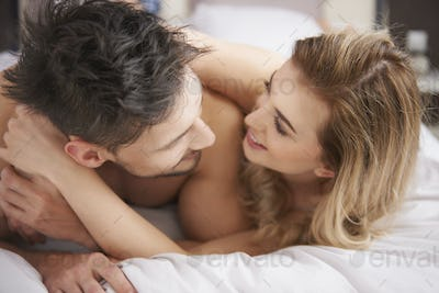 Cheerful couple spending time in the bedroom