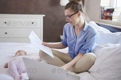 Modern mother working while her child is sleeping