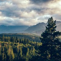 Forest under mountain peaks in clouds at sunset. Tatra Mountains, Poland.