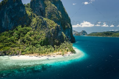 Unique beauty of tropical Pinagbuyutan Island and white sand ipil beach in blue ocean El Nido