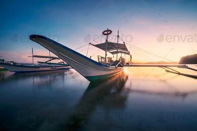 El Nido, Palawan, Philippines. Traditional banca boat in the beach bay in golden sunset light
