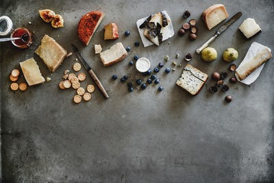 Variety of wine snacks, jam and cheeses over grey background