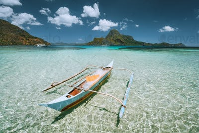 Palawan, Philippines. Traditional small fishing banca boat in front of Cadlao Island in crystal