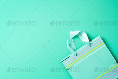 Black friday sale concept. Top view of turquoise paper shopping bag on trendy green background. Copy