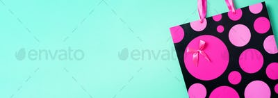 Top view of pink paper shopping bag on trendy green background. Copy space. Gift concept. Woman'