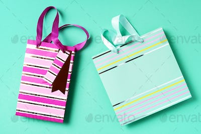 Turquoise and pink paper shopping bag on trendy green background. Top view, copy space. Gift concept