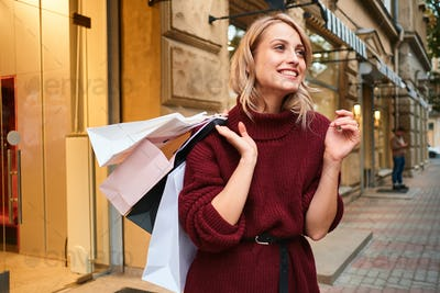 Cheerful blond girl in knitted sweater with shopping bags happily looking away on city street